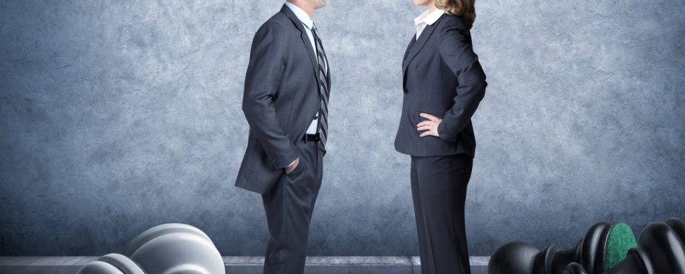 Businessman And Businesswoman Facing Off On Chessboard